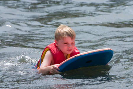 Young boy playing in water on boogie board Stock Photo
