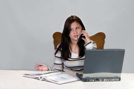 Teenage girl getting help with homework from phone and laptop