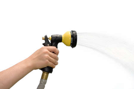 Young hand holding a spraying hose nozzle
