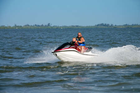 Man and young boy on jet ski photo