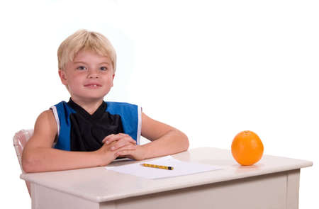 Student sitting at desk with orange for teacher ready for assignment photo