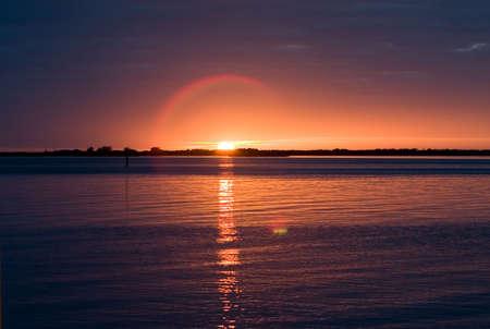 태양 주위 물과 lense 플레어 헤일로에 반영한 탬파 베이를보고있는 일몰