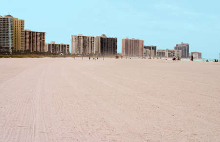 Sandy beach backdropped by city buildings