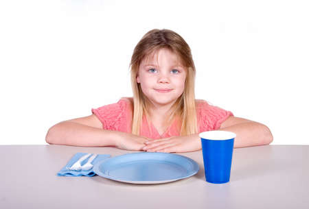 Young girl sitting at table with party type plastic plate, cup, and utensils.