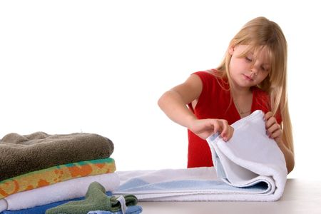 Young girl helping with laundry folding towels