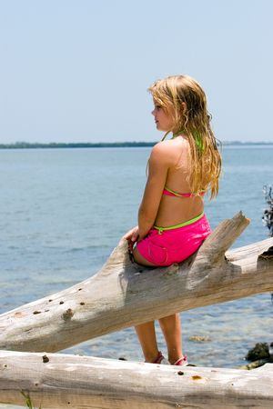 Young girl daydreaming on driftwood at waters edge