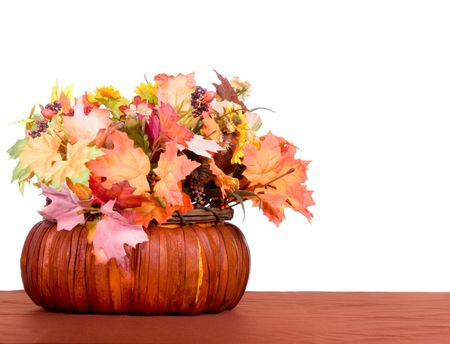 Autumn centerpiece of leaves and berries in a basket on brown table cloth