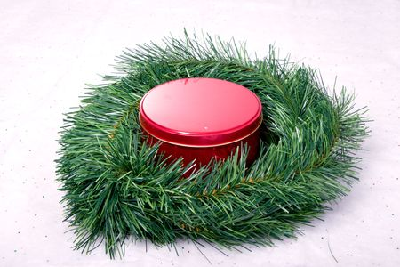 Candy tin sitting in center of pine wreathe Stock Photo
