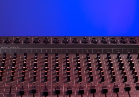 Audio mixing console dramatically lit with red light on blue background