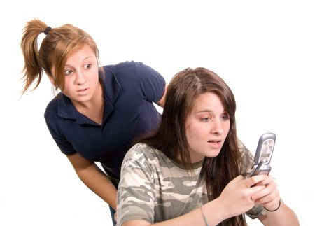 Sisterfriend looking over shoulder shocked at whats on her sisterfriend's cell phone screen