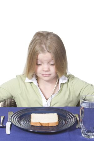 Young girl in disbelief about her bread and water dinner. Stock Photo