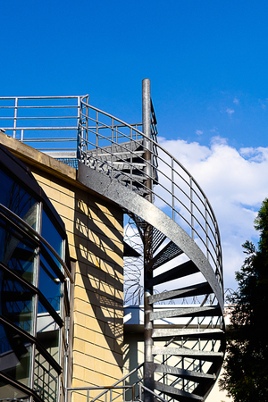 emergency stair: Spiral staircase on the outside of a modern building. Stock Photo