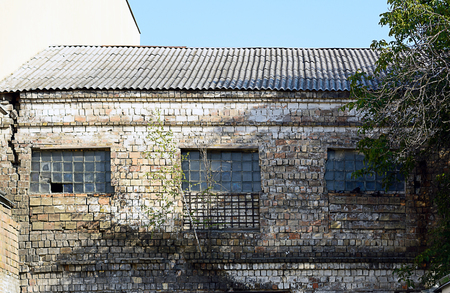 antique factory: Broken windows in an old building on the grounds of an abandoned factory. Stock Photo