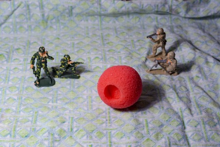 Childrens plastic toys. War and clowning in the foreground. Distraction of other matters from accent.