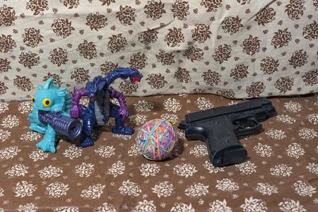 Brinquedos de plástico para crianças. Um dragão de duas cabeças e uma arma ou uma tarefa simples como brincadeira de criança. Armas e defesa, como um ataque deliberado. Foto de archivo - 85076873