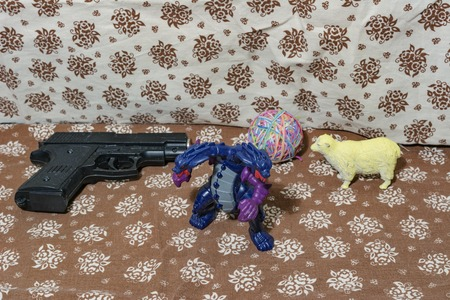 assailant: Childrens plastic toys. A two-headed dragon and a weapon or a simple task as a childs play. Weapons and defense, as a deliberate attack. Stock Photo