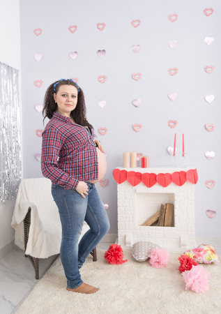 Portrait of wavy-haired pregnant lovely woman standing on a carped near fireplace. Pregnancy concept