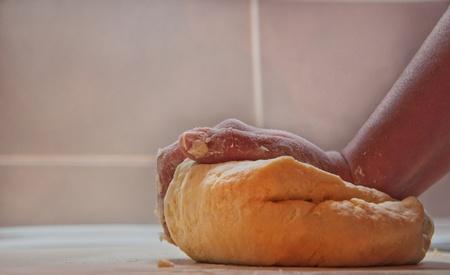 Close-up of female hand kneading domestic dough photo
