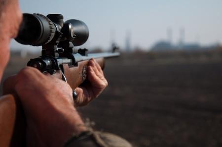 hombre disparando: Cazador que apunta con el rifle de francotirador en el campo Foto de archivo