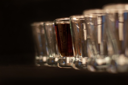 Concept of leadeship with row of empty and one full glass, isolated on black