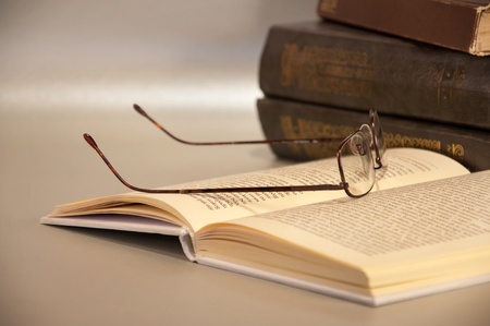 Close up of books and reading glasses isolated on light bacground