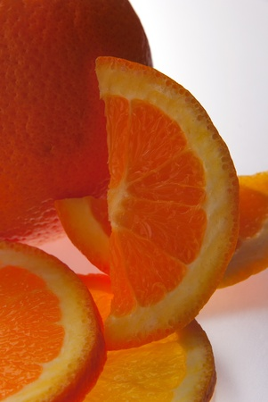 Close up of orange and orange slices isolated on white