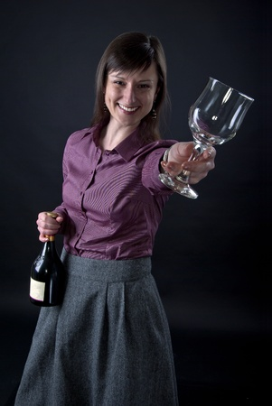 Portrait of beautiful young girl giving a toast with glass and bottle of red wine on black background Stock Photo