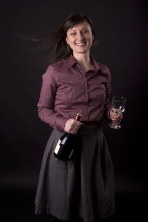 Portrait of beautiful young girl with glass and bottle of red wine on black background
