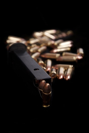 Close up of loaded gun magazine and ammunition isolated on black