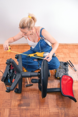 electric drill: Young girl prepairs to repair broken plastic chair Stock Photo