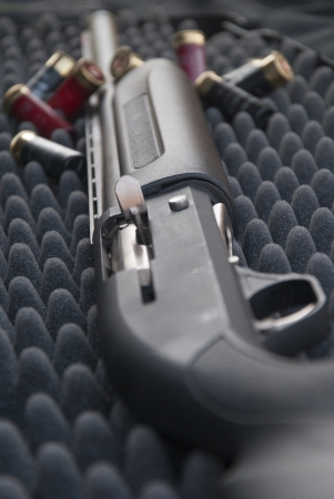 Close up of  shotgun in gray case with buletts photo