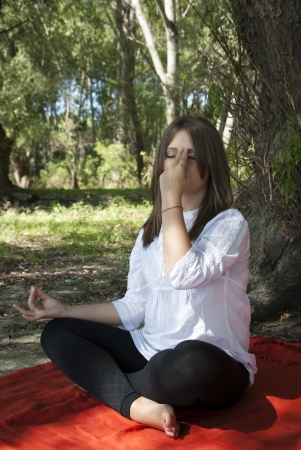 Beautiful girl doing yoga meditation in forest Stock Photo
