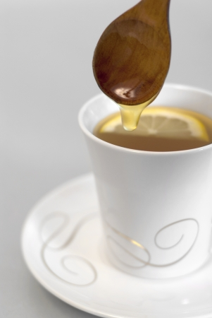 Cup of tea with honey, lemon and wooden spoon Stock Photo