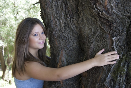 Beautiful young girl hugging a tree