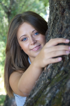 Beautiful girl hugging a tree, concept of unity with nature