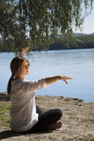 Beautiful girl doing yoga exercise on the river bank