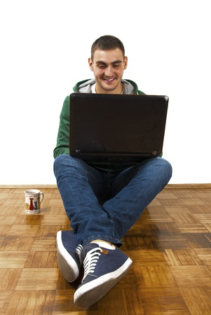 Young male sitting with laptop, chating online with friends