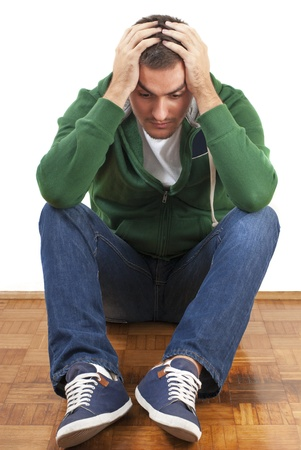 upset man: Young depressed male sitting holding his head with both hands Stock Photo