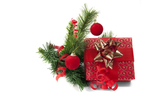 Giftbox wrapped in red paper with crhristmas tree an decoration isolated on white