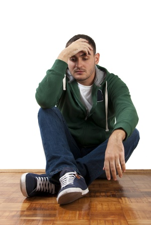 Young depressed male sitting holding his head with hand Stock Photo