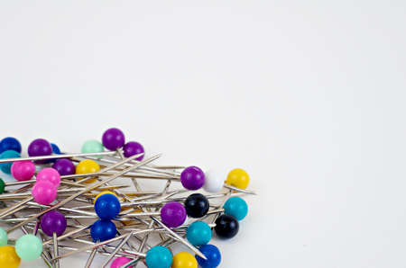 Colorful straight pins in a pile on bottom left of white background  Stock Photo