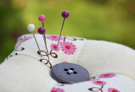 coordinating: Purple flower pincushion with coordinating pins Stock Photo
