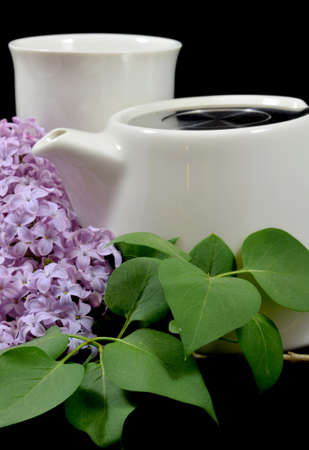 Ceramic teapot and tea cup surrounded by lilacs on a black studio background