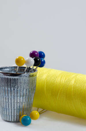 Straight pins standing in a thimble with yellow thread behind on white background
