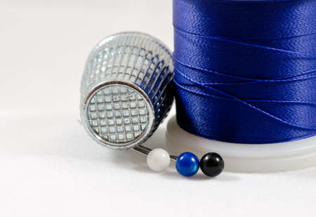 A close up of royal blue thread with a thimble and 3 pins.