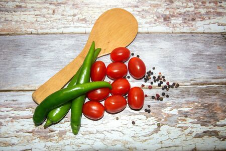 Cherry tomatoes and green chili peppers with a wooden spoon on a wooden table. Nearby pepper peas of different colors are scattered. Gray Boards Background. Illustration for calendar