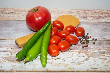 Large tomato, cherry tomatoes and green chili peppers with a wooden spoon on a table of boards. Nearby pepper peas of different colors are scattered. Gray Boards Background. Illustration for calendar