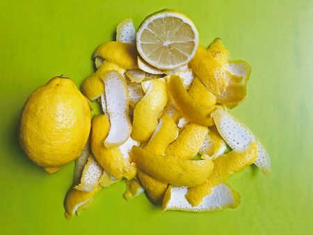 Yellow and white lemon peel on a light green background. Nearby lies a whole lemon and half a lemon. Cooking Limoncello. Ingredients for Lemonade. Stockfoto