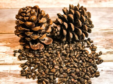 Inshell pine nuts next to two large brown pine cones on a wooden surface from old light brown boards