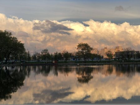 The expanse of the lake with clouds reflected in it, illuminated by sunset. Beautiful clouds at sunset reflected in the water. Beautiful sunset in the metropolis
